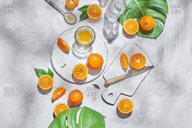 Top view of whole and half of ripe oranges arranged on table with knife and glass with juice