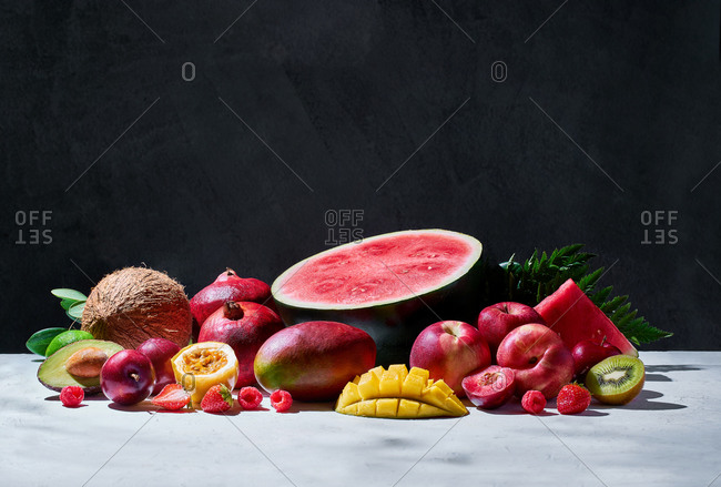 Set of assorted sweet exotic fruits and berries arranged on table in studio