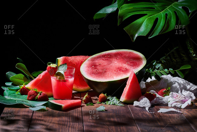 Glass of sweet fruit juice with mint arranged on wooden table with strawberries and ripe watermelon