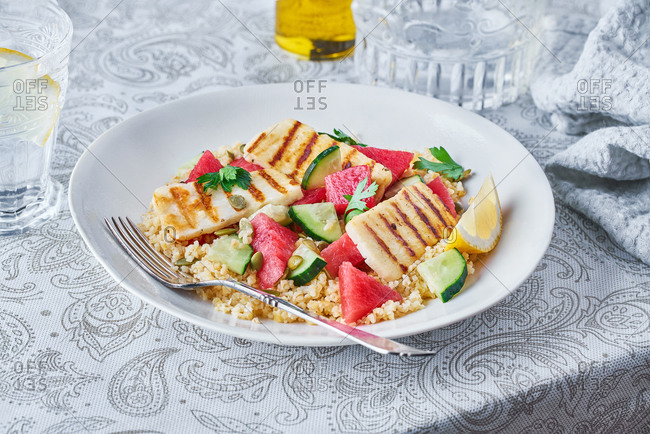 Appetizing Bulgur salad with watermelon and cucumbers in plate served on table for tasty lunch