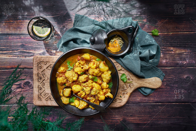 Top view of delicious cauliflower stew with turmeric and vegetables served on wooden table for dinner
