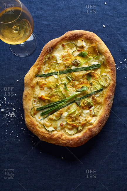 Vegetarian pizza with zucchini flowers, onion, courgette and cheese served with a glass of orange wine