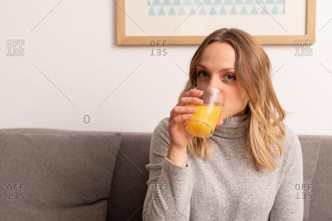 Smiling female sitting on sofa in living room drinking fresh orange juice looking at camera