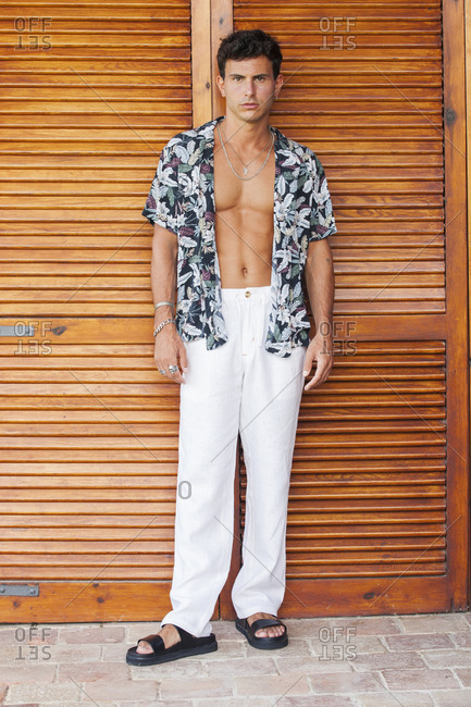 Serious handsome young male in white pants and colorful unbuttoned summer shirt revealing tanned muscular torso standing on terrace against wooden wall and looking at camera