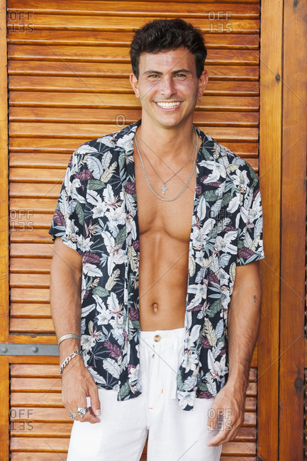 Cheerful handsome young male in white pants and colorful unbuttoned summer shirt revealing tanned muscular torso standing on terrace against wooden wall and looking at camera