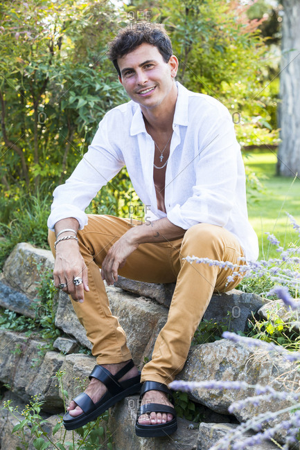 Full length of happy young male in unbuttoned white shirt and colorful jeans with accessories sitting on stone border in green summer garden