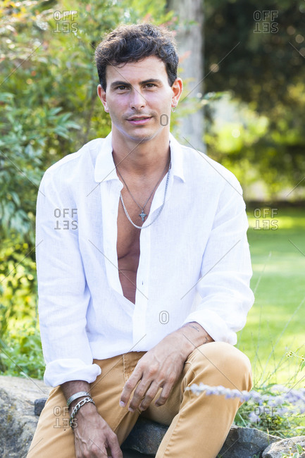Happy young male in unbuttoned white shirt and colorful jeans with accessories sitting on stone border in green summer garden