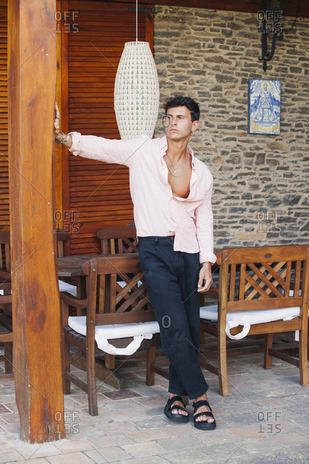 Full body of confident young casually dressed male in unbuttoned shirt and pants leaning on pillar and looking away pensively while standing on rustic terrace with wooden furniture
