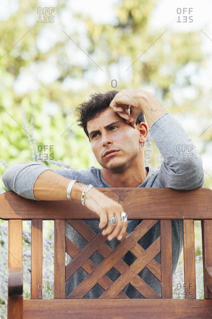 Thoughtful young male in casual clothes with bracelets and finger rings leaning elbow on wooden fence in green garden and looking away