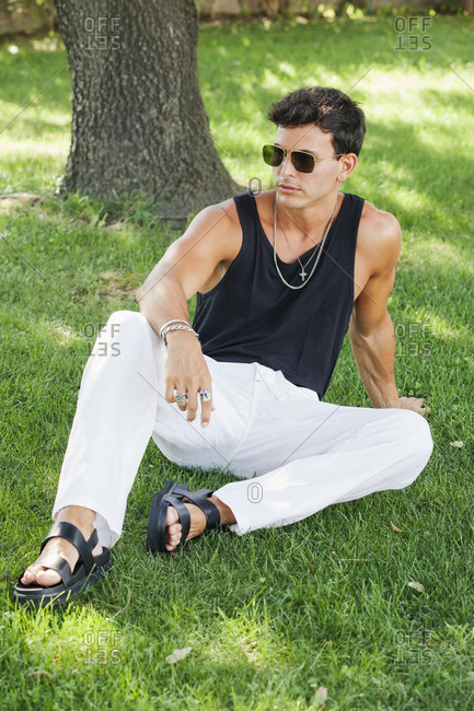 Full body of tanned muscular young male in trendy outfit and sunglasses with stylish accessories sitting on green grass in summer park and looking away