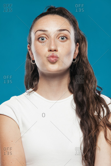 Playful young female sending a kiss to the camera standing against blue background
