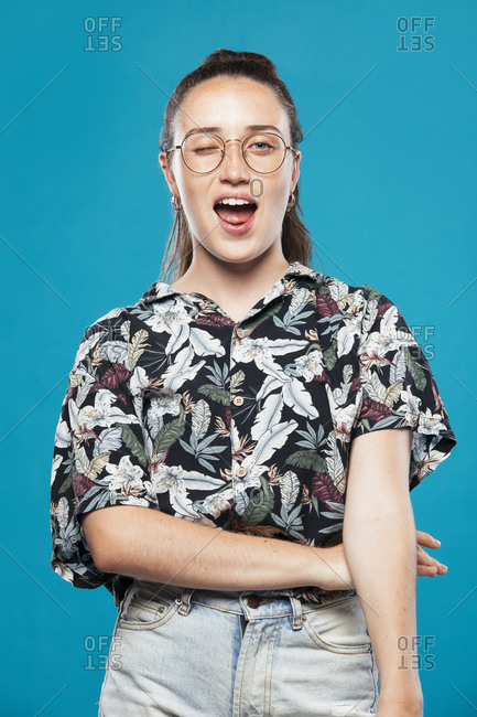 Playful young female in eyeglasses dressed in casual shirt with tropical print and jeans winking at camera against blue background