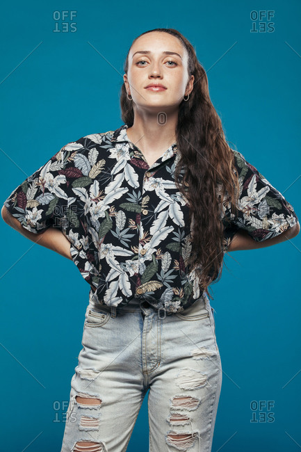 Female teenager model in casual summer clothes standing in blue studio and looking at camera