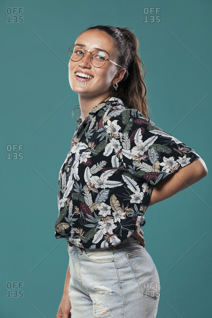 Side view of teen female model in eyeglasses dressed in casual shirt with tropical print and jeans standing in blue studio and looking at camera