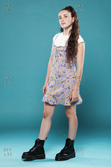 Female teenager model in casual summer clothes and trendy black boots standing in blue studio and looking at camera