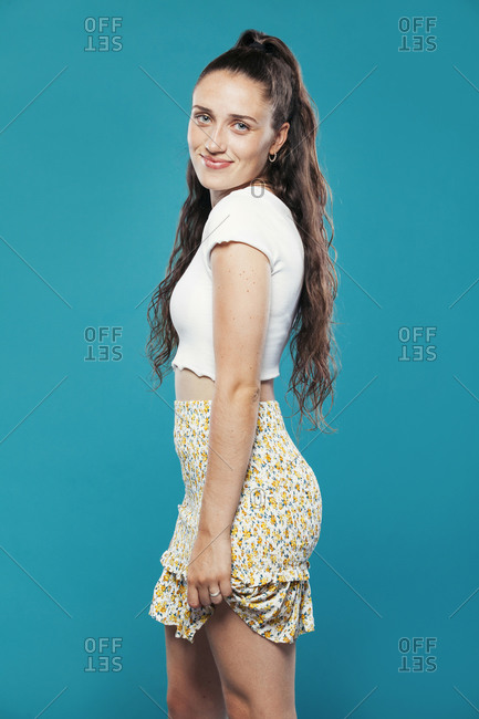 Side view of teen female model in casual summer clothes standing in blue studio and looking at camera