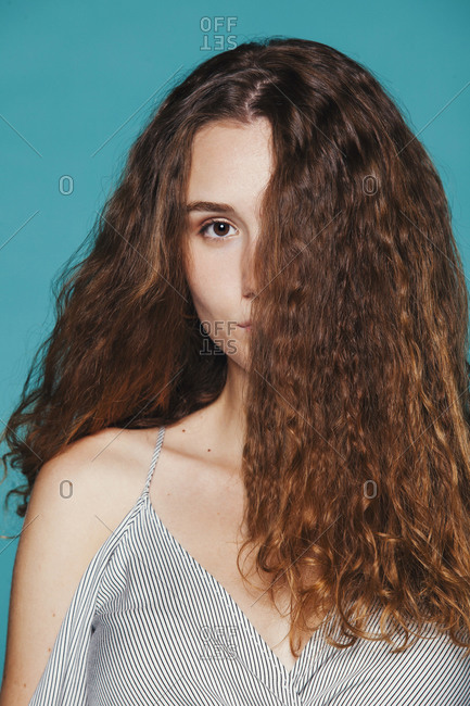Calm female model in casual wear and with long hair covering half of face standing on blue background in studio and looking at camera