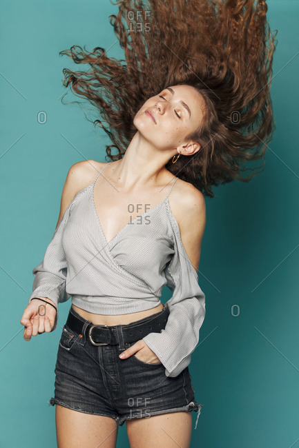 Serene female with long flying hair standing with closed eyes in studio on blue background