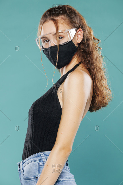 Side view of female wearing medical mask and plastic safety goggles standing on blue background in studio and looking at camera