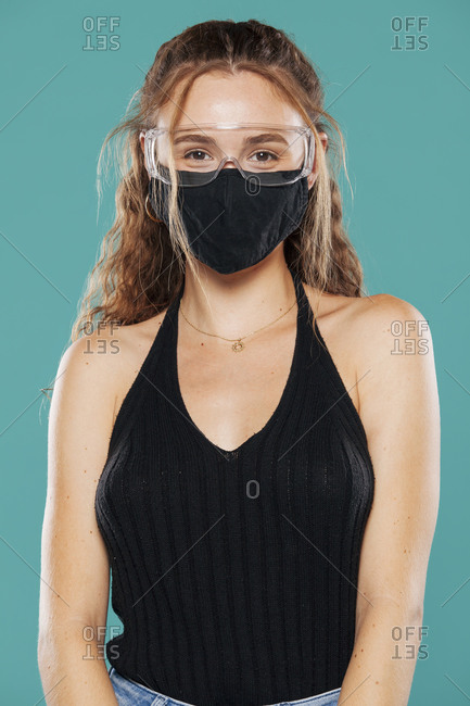 Female wearing medical mask and plastic safety goggles standing on blue background in studio and looking at camera