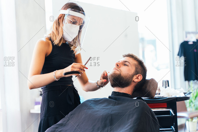 Barber woman in protective mask and face shield shaving male with sharp straight razor while working in barbershop during coronavirus outbreak