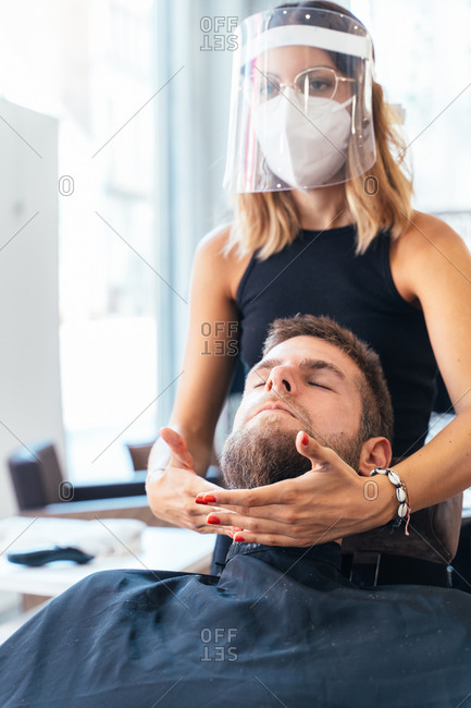Serious female barber in protective shield and mask making massage for relaxing male customer in modern salon