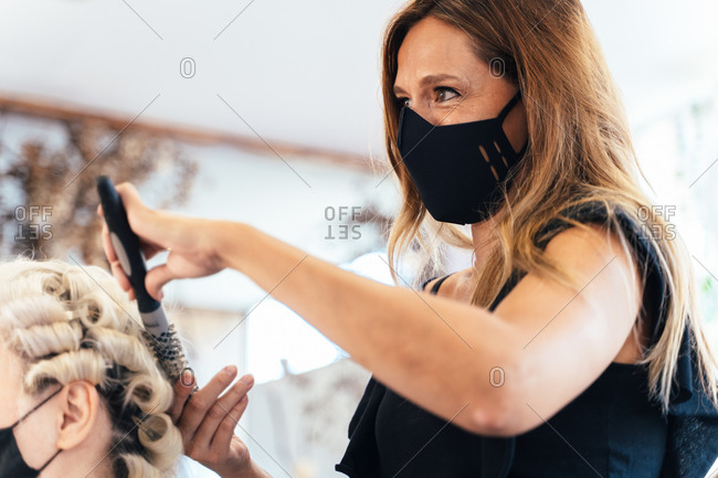 Side view of female stylist in protective mask drying hair of cropped unrecognizable woman sitting in front of mirror in beauty salon