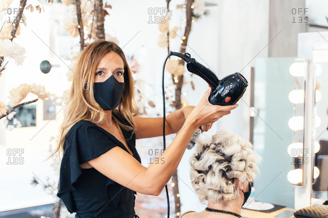 Side view of female stylist in protective mask drying hair of woman sitting in front of mirror in beauty salon
