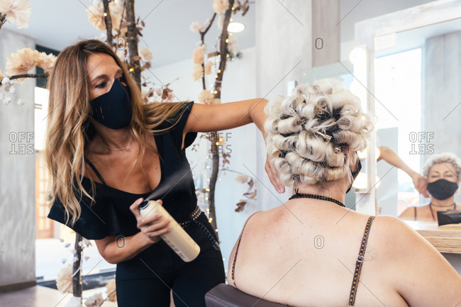 Busy female stylist in protective mask using professional hair spray while making hairdo for female client in salon