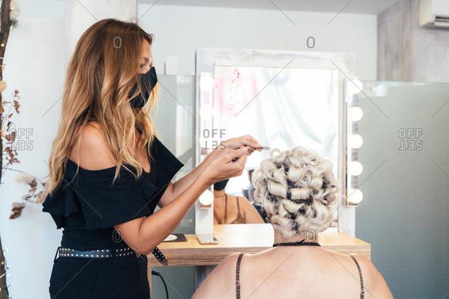 Female hairstylist wearing protective mask working in salon during coronavirus epidemic while making stylish hairdo for customer