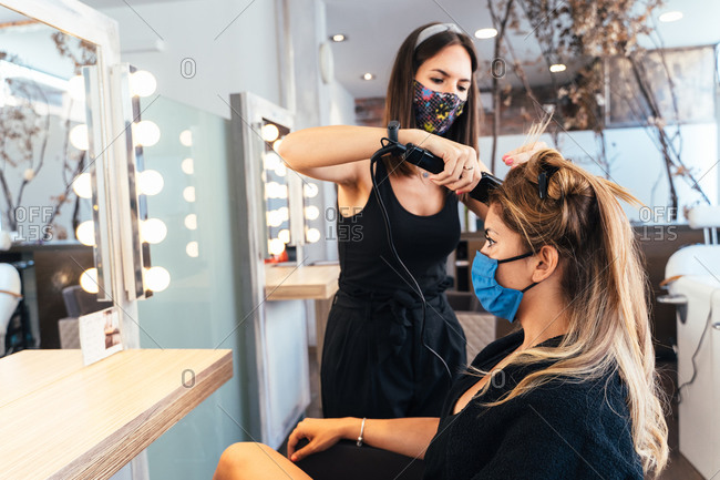 Female hairstylist making hairdo for client while using hair straightener and working in salon during COVID 19 pandemic
