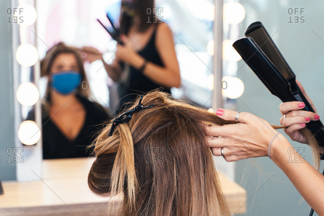 Cropped unrecognizable female hairstylist making hairdo for client with face mask while using hair straightener and working in salon during COVID 19 pandemic