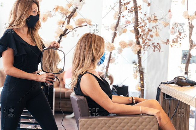 Side view of glad female hairstylist and customer looking in mirror and showing hairstyle to client on a mirror