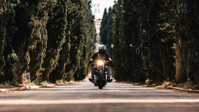 Biker in black leather jackets and helmet riding powerful motorcycle on asphalt road leading between green forest in countryside