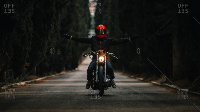Biker in black leather jackets and helmet with open arms riding powerful motorcycle on asphalt road leading between green forest in countryside