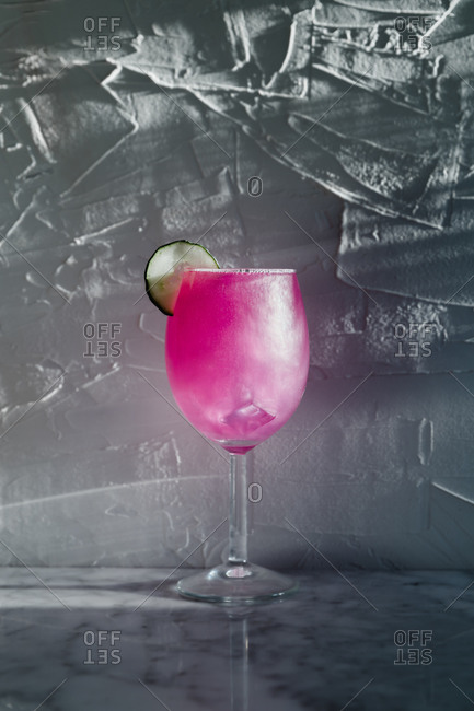 Wineglass of refreshing bright purple cocktail garnished with herbs and sliced lime placed in sunlight against blurred gray background