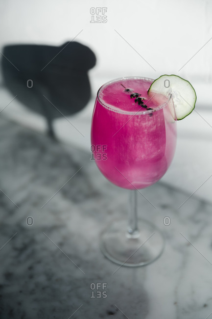 From above of wineglass of refreshing bright purple cocktail garnished with herbs and sliced lime placed in sunlight against blurred gray background