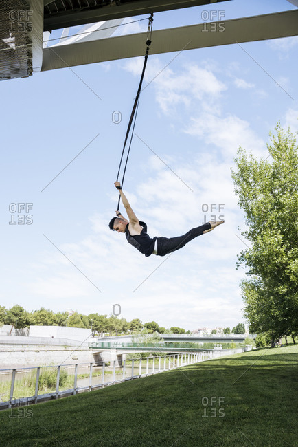 Low angle of fit male gymnast hanging on aerial straps during training in park