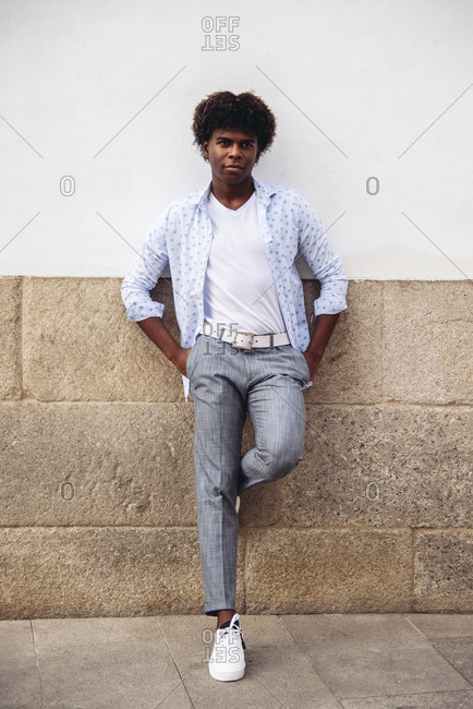 Determined African American male in trendy outfit and with Afro hairstyle leaning on stone wall of building and looking away