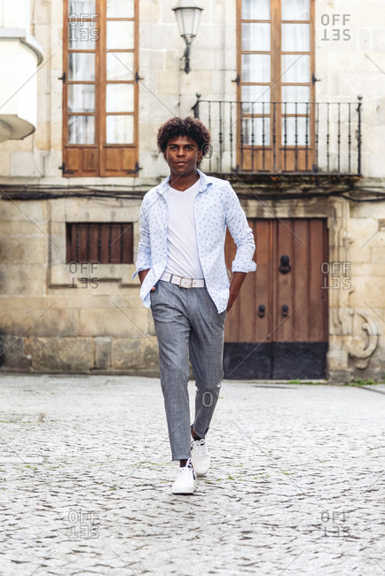 Stylish black male with Afro hairstyle walking with hands in pockets on street and smiling e looking at camera