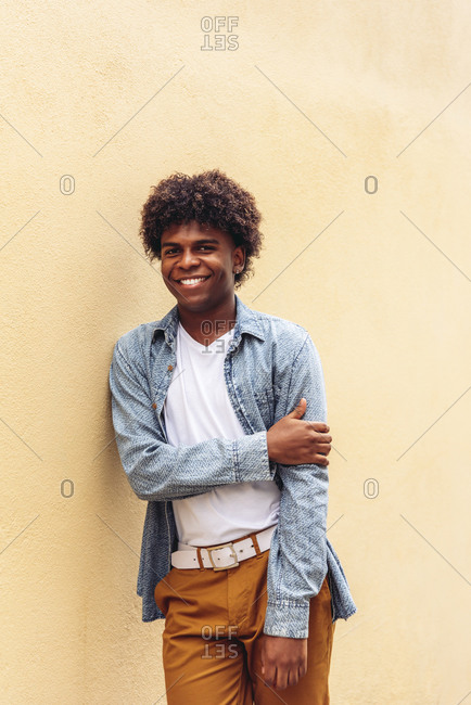 Determined African American male in trendy outfit and with Afro hairstyle leaning on stone wall of building and looking at camera