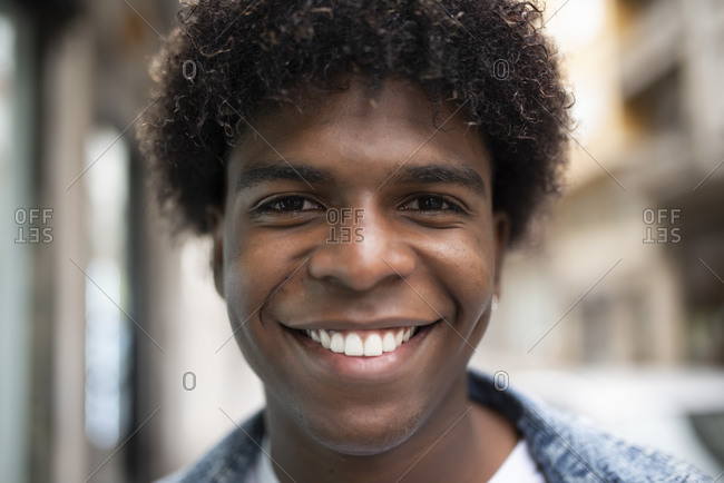 Positive African American male with Afro hairstyle and charismatic smile looking at camera while standing on blurred background of city