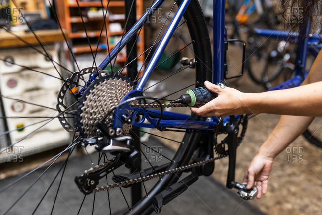 Crop anonymous mechanic putting oil on chain of bicycle while performing maintenance works in workshop