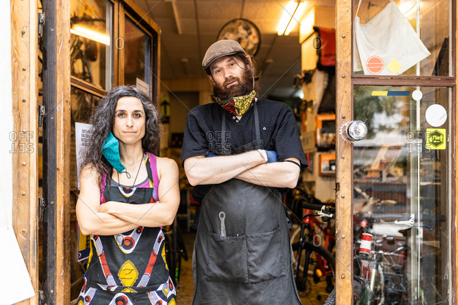 Confident adult ethnic man and woman in workwear with protective masks standing on doorway of bicycle service workshop and looking at camera