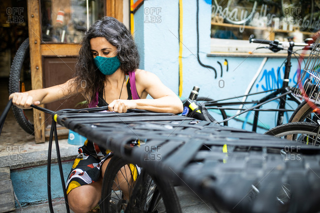 Serious ethnic female technician in protective mask working with tire straps for bikes near workshop entrance