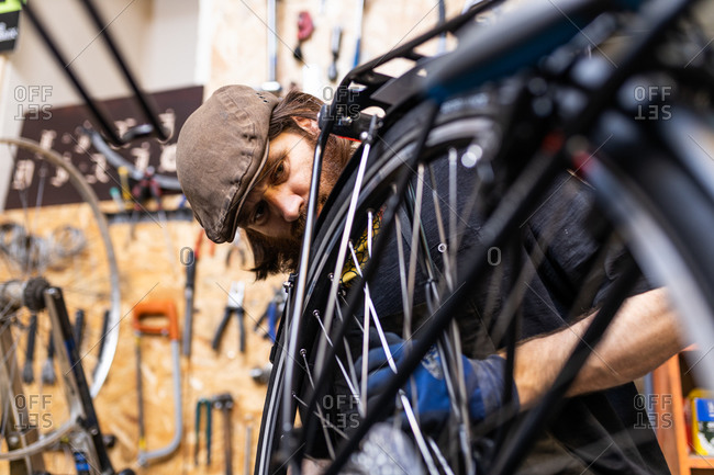 Mature bearded mechanic in workwear and gloves checking and repairing wheel of bike during maintenance service in workshop