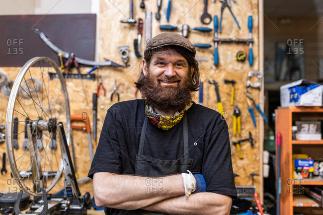 Smiling middle aged bearded craftsman in workwear looking at camera friendly while standing against weathered workbench with various tools in bicycle service workshop