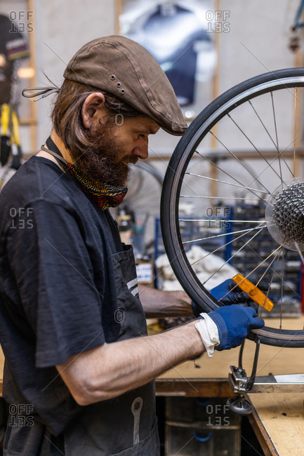 Side view of mature bearded mechanic in workwear and gloves checking and repairing wheel of bike during maintenance service in workshop
