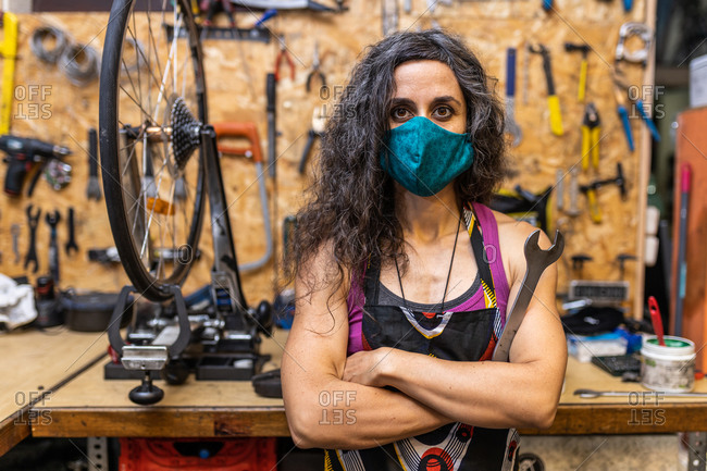 Serious adult ethnic female mechanic in workwear and protective mask holding wrench and looking at camera while standing against weathered workbench with various tools in bicycle service workshop