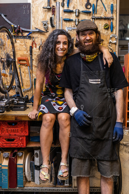 Positive ethnic couple of owners of bicycle service workshop looking at camera and smiling friendly against weathered wall with various repair instruments